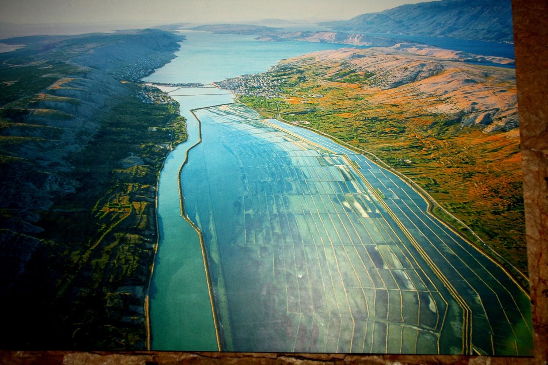 V spodnjem in osrednjem delu fotografije so soline. Vmes je mesto Pag, sledi paški zaliv. Desno, tik ob solinah teče cesta, glavna žila prometnica, ki se vije po sredi celotnega otoka.