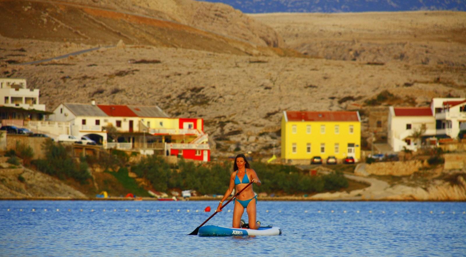 S supom na dopust. Ali počitnice. SUP je okrajšava angleškega poimenovanja Stand up paddling (tudi Stand up paddle surf) za šport, pri katerem stojiš in veslaš. Stojimo, veslamo, opazujemo in občudujemo naravne lepote.