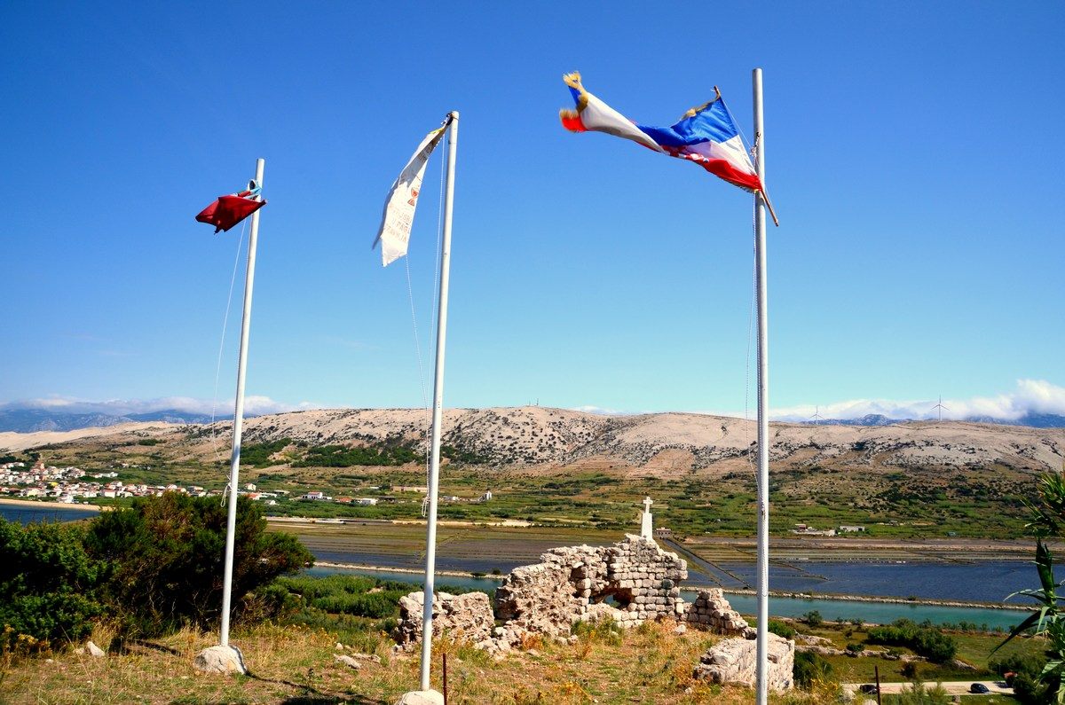 Plapolajo zastave. Nižje v dolini so soline.