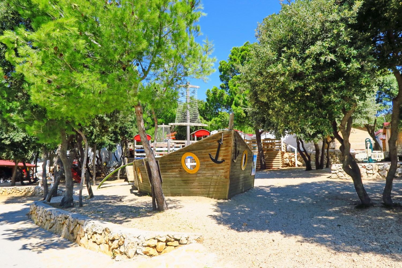 Na južni strani otoka Pag leži Camping Village Šimuni, obdan z borovci in cvetovi oleandra.