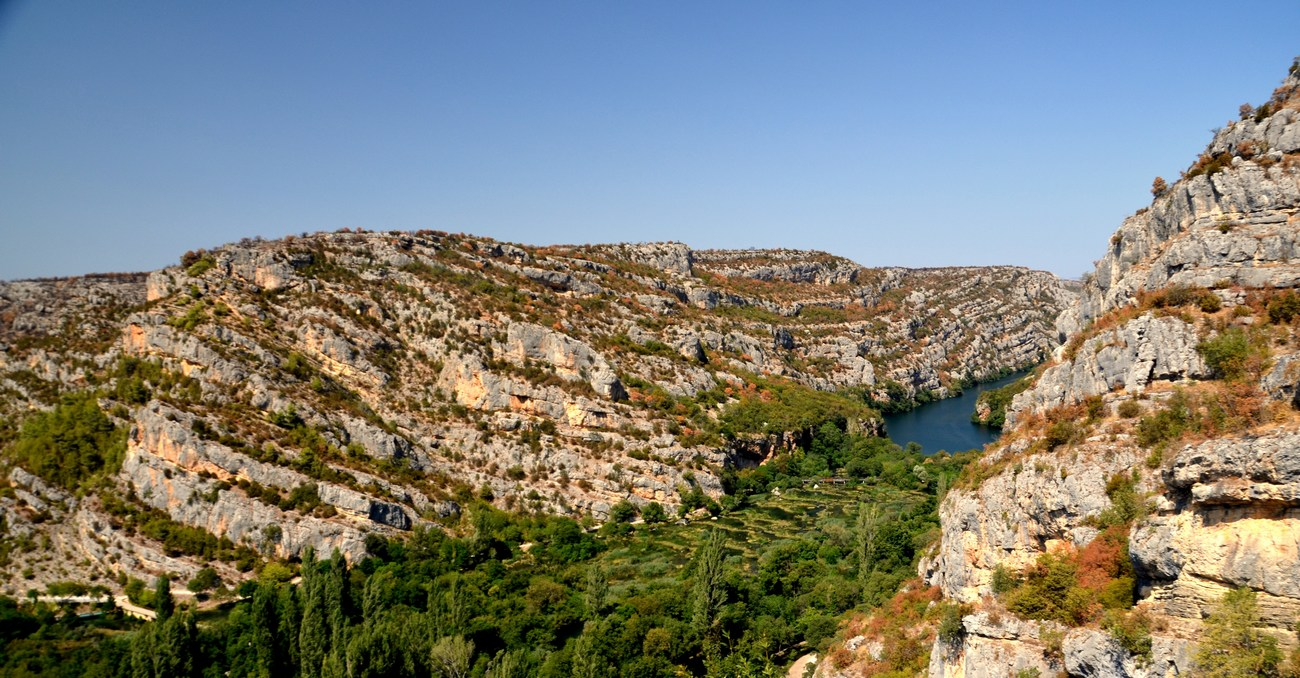 Na sliki je Lehnjakova pregrada, dolga kar 650 m in široka do 450 m, se prične s številnimi malimi brzicami, ki so jih domačini poimenovali Ogrlice