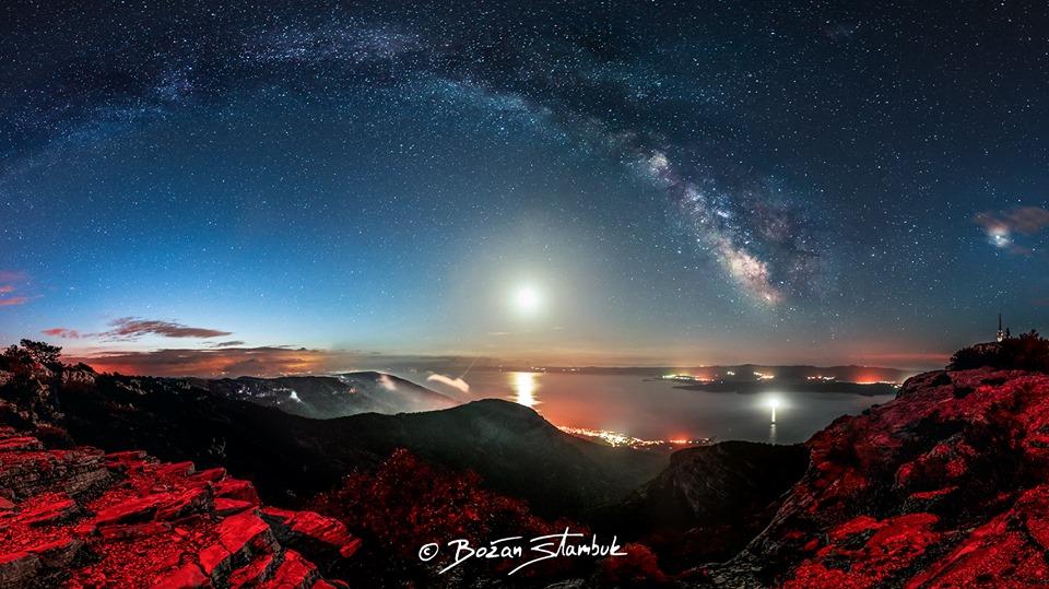 Nočna panorama z Vidove gore, ki je najvišja gora vseh hrvaških otokov. Z leve strani sonce počasi leze izza oblakov. Svetloba Lune pronica skozi meglo, ki se spušča proti Bolu, Zlatnemu ratu in Hvaru. Mlečna cesta dominira.