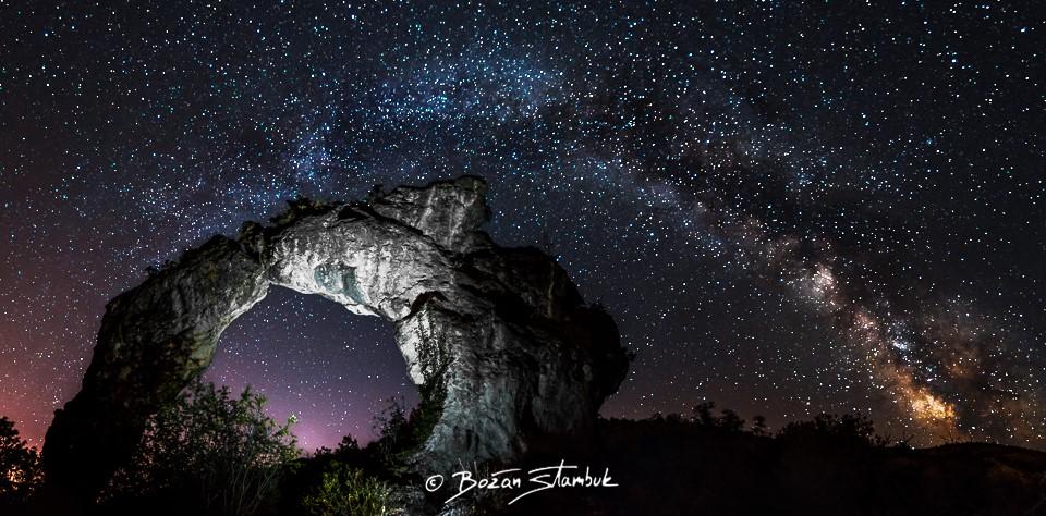 Panorama nočnega neba in Mlečne ceste iznad naravnega fenomena Koloč, blizu kraja Nerežišče. Dve ogromni skali sta se naslonili ena na drugo, vzpostavili sta kamniti lok.
