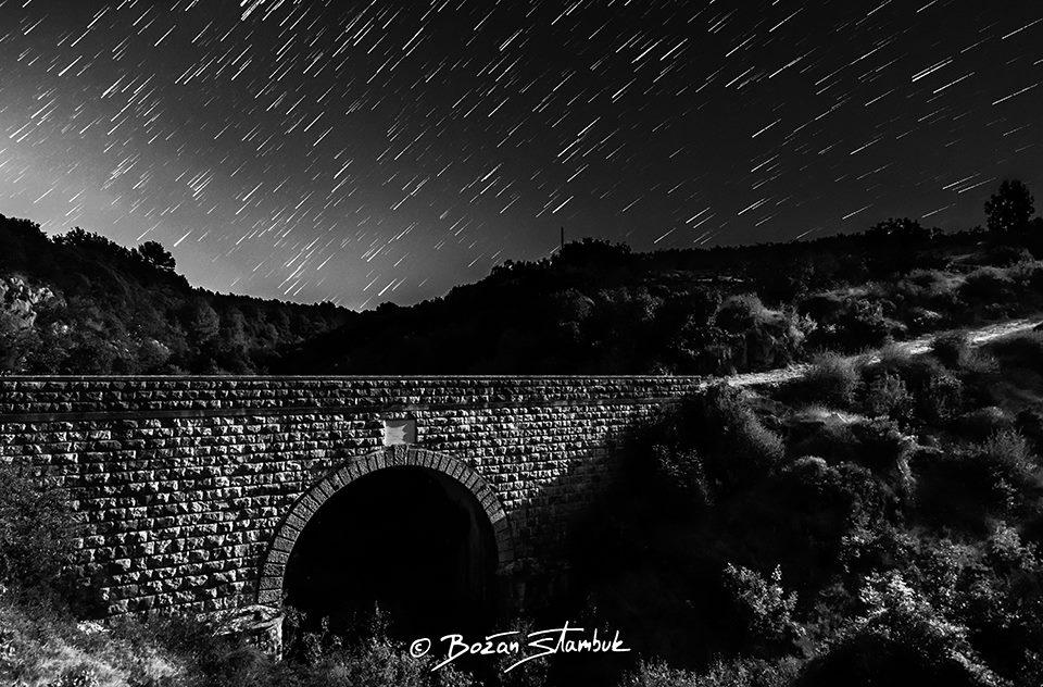 Gibanje zvezd in njihovi sledovi nad mostom Franje Josipa, KIžišća, otok Brač. Most je bil zgrajen v 19. stoletju in je sedaj zaščiten spomenik.