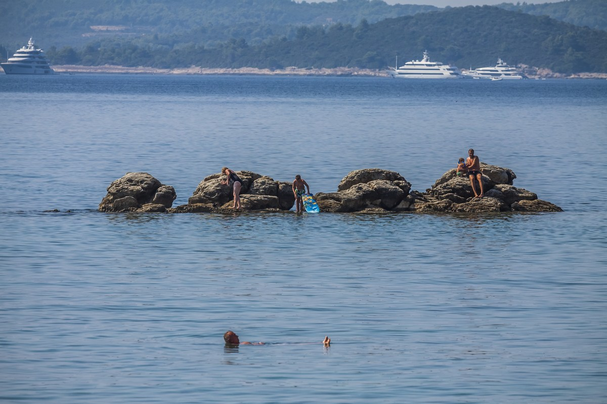 Plavalci, razkošne jahte v ozadju
